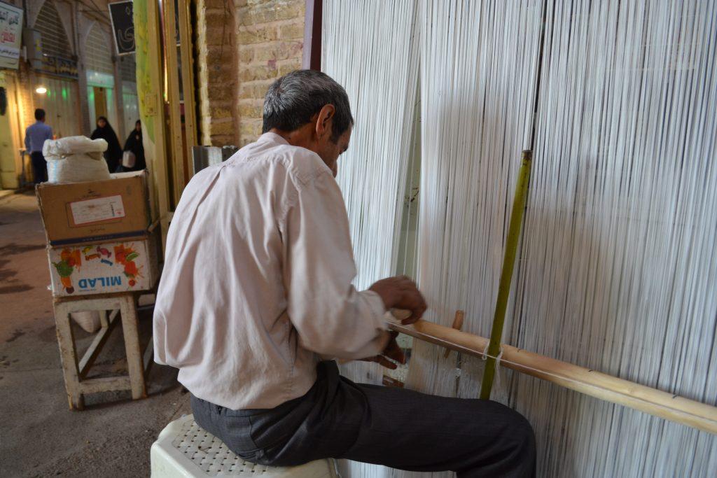 イランイスファハーンのバザールにて、絨毯の整経作業をしている男性